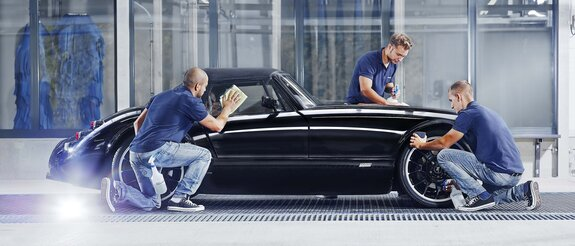 Employees clean a luxury car by hand in the car wash