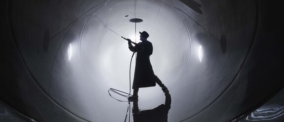 Man in safety clothing stands in a pipe and cleans it with a high-pressure cleaner