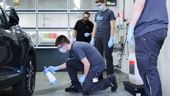 Employee showing an apprentice how to apply a Koch-Chemie product on a car's engine hood with a polishing machine