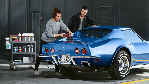 Woman and man polishing a blue Corvette
