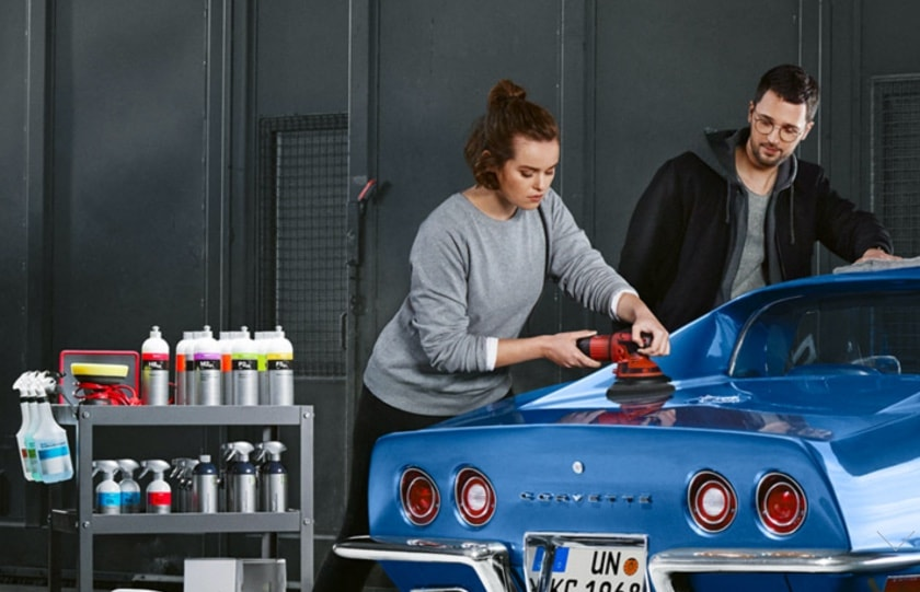 Woman polishing a blue sports car with a polishing machine with a man standing nearby